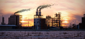 Raffinerie de pétrole au coucher du soleil. Pollution d'environnement. Photographie stock libre de droits