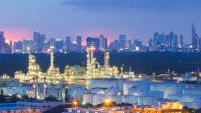 Raffinerie industrielle pétrochimique avec le fond de ville après coucher du soleil Photos libres de droits