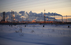 Raffinerie am Sonnenunterganghimmelhintergrund Eisiger Abend des verschneiten Winters Lizenzfreie Stockfotografie