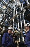 Raffineriearbeitskräfte und Rohrleitungstation Stockbild
