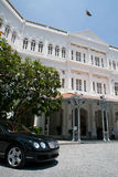 Raffles Hotel and Waiting Car in Singapore. Raffles Hotel in Singapore on a clear autumn day Royalty Free Stock Photo