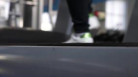 Rafforzamento dei muscoli della gamba camminando Primo piano Cardio carico Treni della ragazza su una pedana mobile Camminando in archivi video