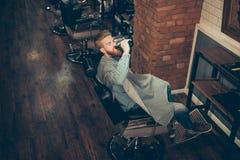 Raffreddi fuori al negozio di barbiere Vista laterale di youn alla moda bello fotografie stock libere da diritti