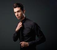 Raffreddi il giovane in camicia nera e leghi Immagini Stock
