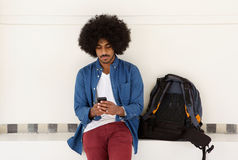Raffreddi il tipo di viaggio che si siede con il telefono cellulare e la borsa Fotografia Stock Libera da Diritti
