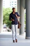 Raffreddi il tipo nero che cammina nella città con il telefono cellulare e la borsa Immagine Stock