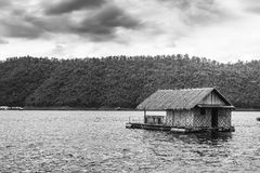 Raft house on green water black and white. Raft house on green water black and white at the lake with mountain background Stock Photo