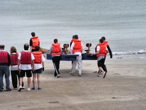 Raft Race. A team carrying their raft towards the sea for the start of the raft race at a local gala Royalty Free Stock Image