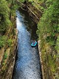 Rafters in Ausable Chasm. Rafters are guided down a peaceful sunlit river in Ausable Chasm, Kesseville, New York. Green leaf trees cover canyon walls in this royalty free stock image