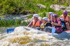 Rafting. Cheerful group of people aged are sailing on a rubber inflatable boat. Positive emotions, adrenaline. Myhiya, Ukraine - May 1, 2018: Rafting. Cheerful stock photography