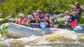 Rafting. Cheerful group of people aged are sailing on a rubber inflatable boat. Positive emotions, adrenaline. Myhiya, Ukraine - May 1, 2018: Rafting. Cheerful stock image