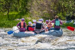 Rafting. Cheerful group of people aged are sailing on a rubber inflatable boat. Positive emotions, adrenaline. Myhiya, Ukraine - May 1, 2018: Rafting. Cheerful royalty free stock photo
