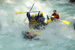 Rafting. A group of people is doing a rafting / all of them wearing jackets and rescue hardhat / water splashing everywhere Royalty Free Stock Image