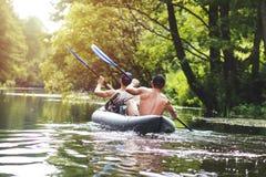 Rafting op de rivier in een kajak in de zomer leisure Twee mensen in de bootrij met roeispanen stock foto