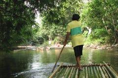 Rafting på bambuflottar på en bergflod i Khao Lak parkera, Thailand Mannen kontrollerar flotten med en lång pol, bakre sikt fotografering för bildbyråer