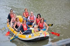 Rafting , Smiling happy people on a rubber-boat rafting on calm waters stock images