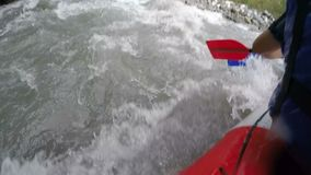 Rafting team facing huge waves, rocks and hazards, dangerous extreme sports. Stock footage stock video footage
