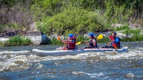 Rafting. Three sportsmen are sailing on a rubber inflatable boat. Teamwork. Water splashes close-up. Ecological tourism royalty free stock photo