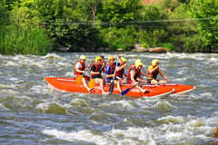 Rafting tourists with an experienced instructor on the river. NIKOLAEV, VILLAGE GRUSHEVKA, UKRAINE - MAY 23, 2014: Rafting tourists with an experienced royalty free stock photo