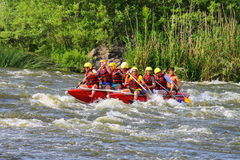 Rafting tourists with an experienced instructor on the river. NIKOLAEV, VILLAGE GRUSHEVKA, UKRAINE - MAY 23, 2014: Rafting tourists with an experienced royalty free stock images