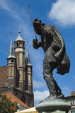 Raftsman in Torun, Poland. Statue of raftsman playing the violin with the tower of the church in the background, Torun, Poland stock photo