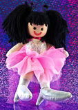 Cute rag doll. Rag doll with masses of black hair, frilly pink party dress and white high heeled boots on a purple  background Stock Image