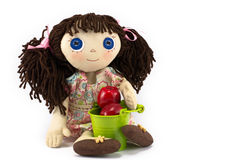 Rag doll girl with brown hair near green bucket with red apples on white background Royalty Free Stock Images