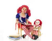 Rag Doll Reading to Her Baby. An adorable elementary rag doll reading to her dolly with a small stack of books nearby.   Both rag dolls are sitting in their Stock Photography