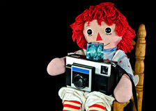 Rag doll with retro camera Stock Images