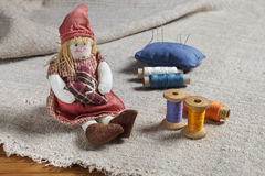Rag Doll and sewing items. The table is covered with a rough cloth. Doll, spools of thread and needles Royalty Free Stock Photography