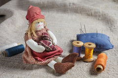 Rag Doll and sewing items. The table is covered with a rough cloth. Doll, spools of thread and needles Stock Photos