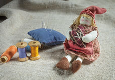 Rag Doll and sewing items. The table is covered with a rough cloth. Doll, spools of thread and needles Stock Photo
