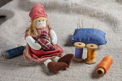 Rag Doll and sewing items. The table is covered with a rough cloth. Doll, spools of thread and needles Stock Photography