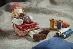 Rag Doll and sewing items. The table is covered with a rough cloth. Doll, spools of thread and needles Royalty Free Stock Photos