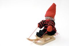 Rag doll on toy sled. A view of a small, handmade rag doll with an orange knit hat, sitting on a tiny wooden sled.  Isolated against a white background Royalty Free Stock Images