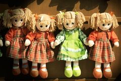 Rag dolls girls. Vintage toys. Four rag dolls girls. Some rag dolls in a row seems to be held by hand. Vignette with vintage retro colors Royalty Free Stock Photos