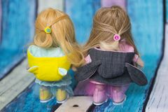 Rag dolls with long fair hair dressed in funny jacket with hoods and yellow and pink sneakers. Handmade rag dolls with long fair hair dressed in funny jacket royalty free stock photos