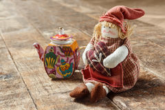 Rag dolls and tea on a wooden table. Small decorative porcelain teapot. Handmade doll Royalty Free Stock Photo