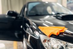 Rag on the hood of clean car on carwash service. Rag on the hood of clean car with open doors, nobody. Professional dry cleaning of car on carwash service royalty free stock photography