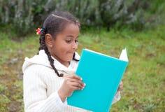 Ragazza abbastanza africana nel parco che legge un libro Immagini Stock Libere da Diritti