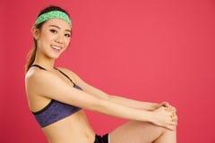 Ragazza abbastanza asiatica che allunga mentre facendo aerobica e yoga in a immagine stock libera da diritti