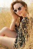 Ragazza abbastanza bionda che si rilassa sul campo con erba asciutta Immagine Stock Libera da Diritti