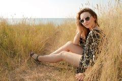 Ragazza abbastanza bionda che si rilassa sul campo con erba asciutta Fotografia Stock