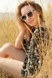 Ragazza abbastanza bionda che si rilassa sul campo con erba asciutta Immagini Stock