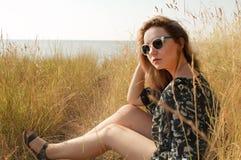 Ragazza abbastanza bionda che si rilassa sul campo con erba asciutta Fotografia Stock Libera da Diritti