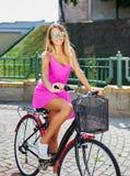 Ragazza abbastanza felice in vestito rosa ed occhiali da sole che si siedono su un bicy fotografie stock libere da diritti