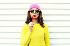 Ragazza abbastanza fresca di modo del ritratto con la lecca-lecca che soffia le labbra rosse in vestiti variopinti sopra fondo bi Fotografia Stock