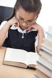 Ragazza abbastanza giovane del banco che legge un libro immagine stock