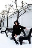 Ragazza abbastanza moderna dei pantaloni a vita bassa dei giovani che aspetta sul banco al parco della neve di inverno da solo, c Fotografia Stock