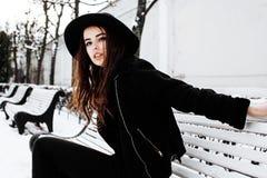 Ragazza abbastanza moderna dei pantaloni a vita bassa dei giovani che aspetta sul banco al parco della neve di inverno da solo, c Immagini Stock